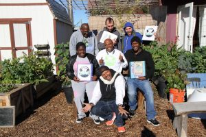 Grassroots canvassers pose in the garden. (Credit: Planting Justice