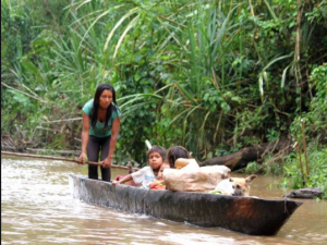 Indigenous family traveling by canoe on the Bobonaza River in the Ecuadorian Amazon (Credit: The Ecologist)