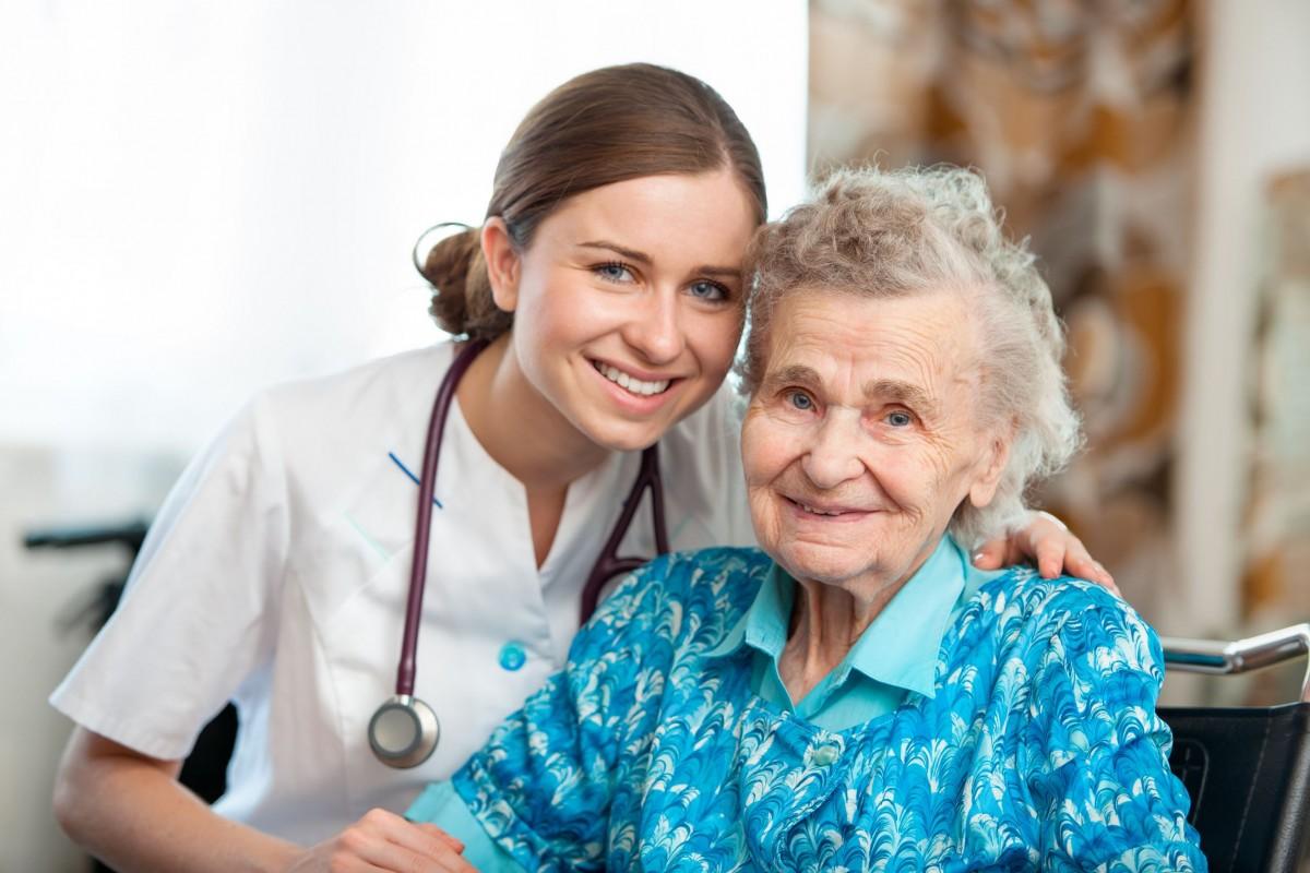 A senior and a nurse smiling into the camera.