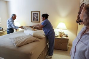 An in-home caregiver helps a client change bedding, from The Atlantic.