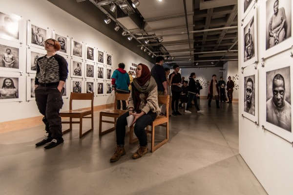 "Gallery-goers watching ""Take a Picture, Tell a Story""-Robert Gumpert (Photo by Ryan Richardson)"